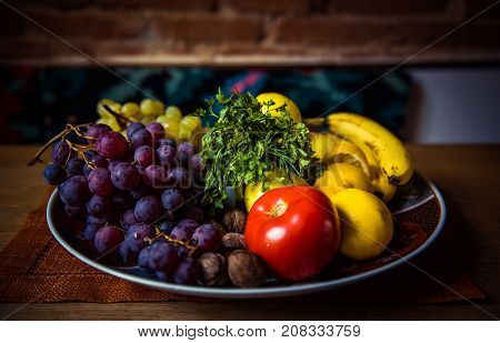 Assortment Of Juicy Fruits In A Plate On Wooden Table