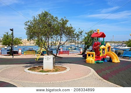 BIRZEBBUGA, MALTA - APRIL 1, 2017 - Childrens playground with the harbour to the rear Birzebbuga Malta Europe, April 1, 2017.