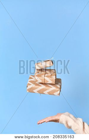 Woman's hands trying to catch gift box. Christmas or new year decorated gift box