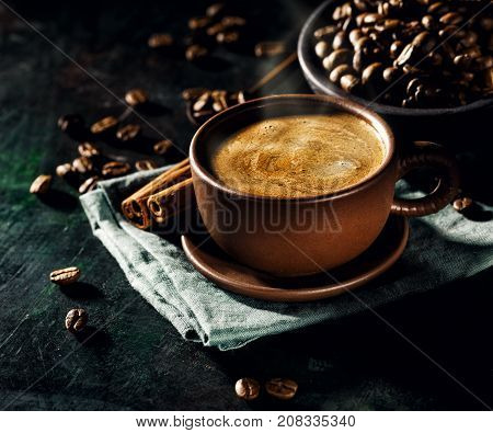 Cup of freshly brewed coffee composed on black with coffee beans and cinnamon sticks.