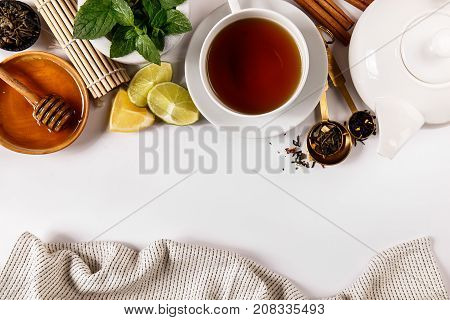 Top view of delicious tea additives and cup of tea composed on white.
