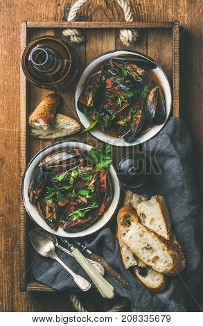 Flat-lay of Belgian boiled mussels in tomato sauce with fresh parsley in serving metal bowls in wooden tray, baguette bread slices and light beer in bottle over rustic table background, top view