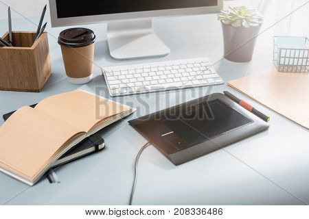 The desk with laptop, notepad with blank sheet, pot of flower, stylus and tablet for retouching. Workspace of professional retoucher. Creativity, design, art and modern equipments concept