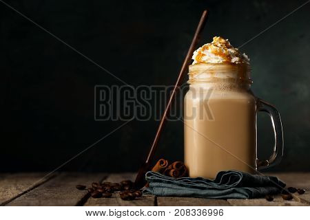 Transparent mug with tasty coffee composed with beans and wooden spoon on black background.