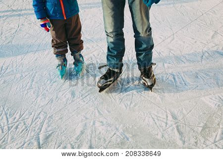 father with little son skating together, family winter sport