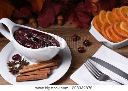 Closeup of a gravy boat with fresh homemade cranberry sauce on a Thanksgiving table.