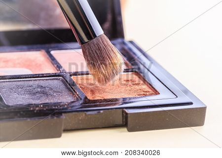 Brush for make-up over a set of eye shadow close-ups