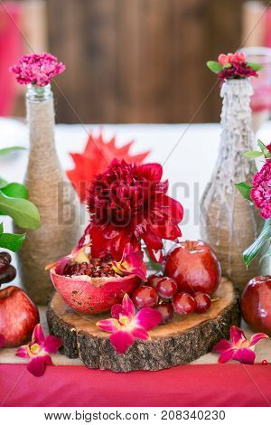 decoration with bottles, garnet and grapes on the wooden small plate
