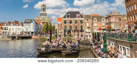LEIDEN, NETHERLANDS - SEPTEMBER 03, 2017: Panorama of people enjoying the sun in the center of Leiden Holland