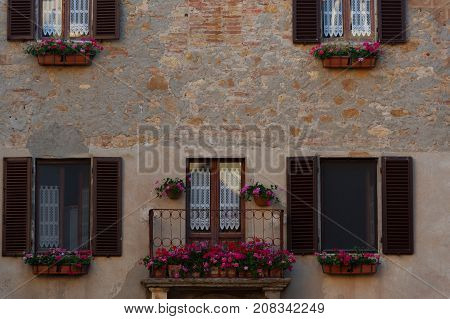 Pienza, Italy - May 27, 2017: Old tuscany balcony with geranium flowers in the small magical and old village of Pienza, Val D'Orcia Tuscany - Italy
