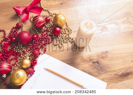 Conceptual image with a letter addressed to Santa on a wooden table surrounded by Christmas decorations and a lit candle.