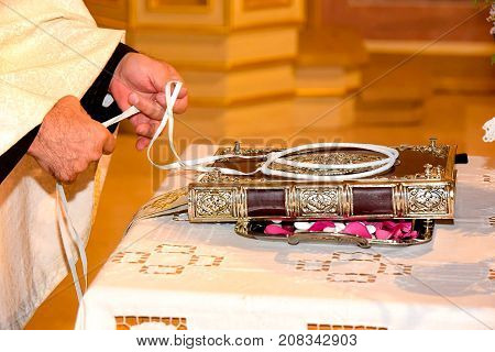 Orthodox Cristian priest hands and wedding crowns decorated on a gospel preparing for ceremony.