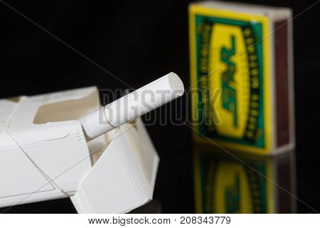 Cigarette sticking out from the pack and matches on black