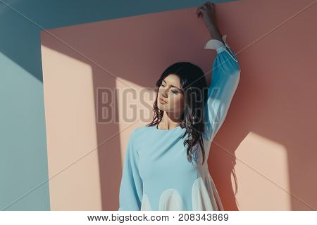 Beautiful woman standing in fashionable turquoise dress with long sleeves and looking down
