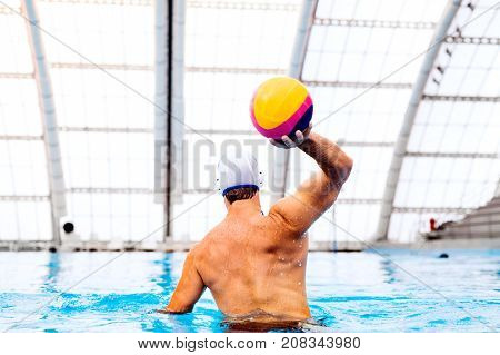 Water polo player in a swimming pool. Man doing sport. Rear view.