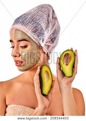 Avocado clay face mask. Woman in medical hat holding half of green fruit with stones isolated background. Facial beautiful procedure concept. Skin softening.