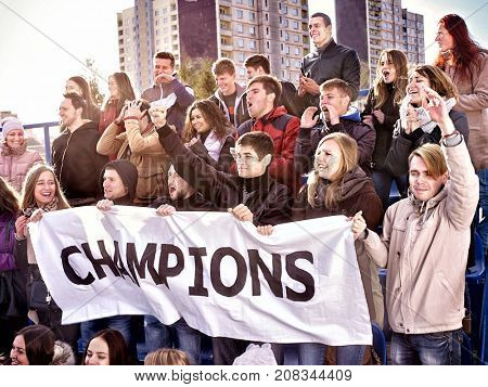 Fans cheering in stadium holding champion banner and singing on tribunes. Large group young people together support your favorite team. Cold weather outdoor. Beginning of football match.