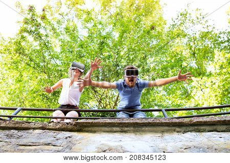 Beautiful young couple on a walk in town, standing on a bridge, wearing virtual reality goggles . Sunny spring day.