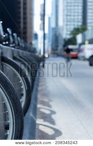 person riding a bike on a busy city street with Toronto streetcar cars and skyscrapers in the background and a row of wheel and bike at a bike rental station