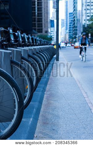 person riding a bike on a busy city street with cars and skyscrapers in the background and a row of wheel and bike at a bike rental station