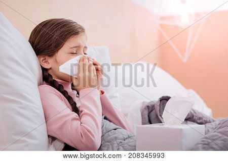 Sneeze. Little tired ill child sneezing with her eyes closed while leaning on a pillow