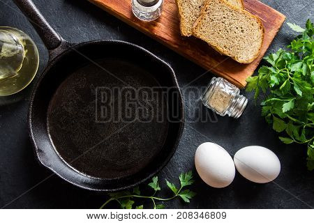 Frying pan and eggs. Close up view of ingredients of fried egg and a frying pan. Empty cast iron pan eggs salt pepper oil and parsley on black background for cooking fried eggs.