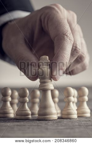 Man Playing Chess Moving The King Piece Lifting It Up In His Fingers In A Close Up View
