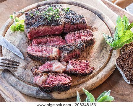 Medium rare Ribeye steak or beef steak on the wooden tray with herbs.