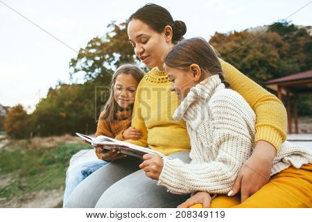Family spending time together outdoors in autumn. Mom with her daughters reading book in park. Fall weekend in the open air.