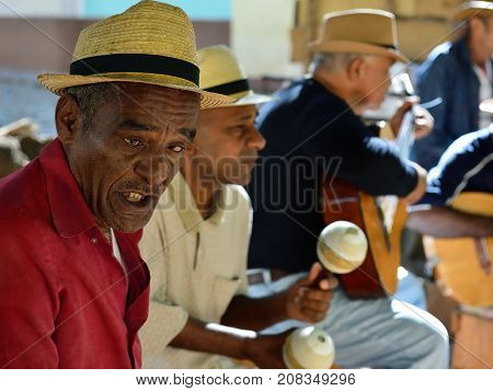 TRINIDAD CUBA - 08 NOVEMBER 2016: Portrait of Latino American men of musicians play on maracases guitar and small drums and sing songs