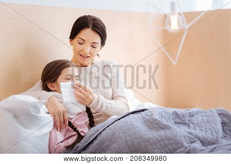 Helpful woman. Nice cheerful woman helping her daughter to blow her nose by holding a napkin