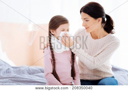 Cheerful mother. Smiling cheerful young mother being very kind while helping her child to blow the nose