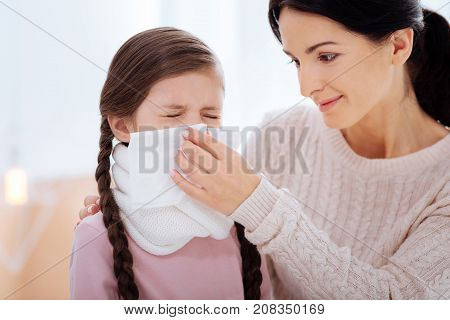Little help. Kind loving young mother helping her little ill daughter while holding a napkin for her