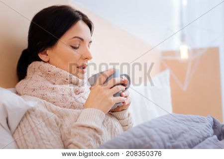 Ill woman. Unhappy ill young woman looking at her pink cup while being in a bed