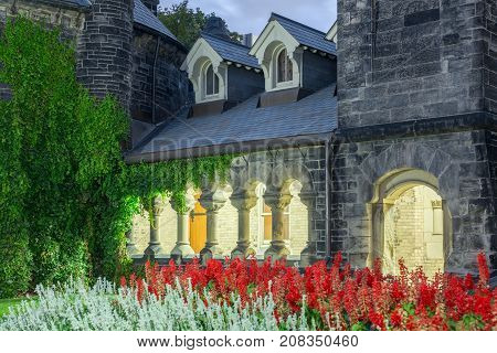 red and white flower patch in front of classic stone building with arc door pillars passage way