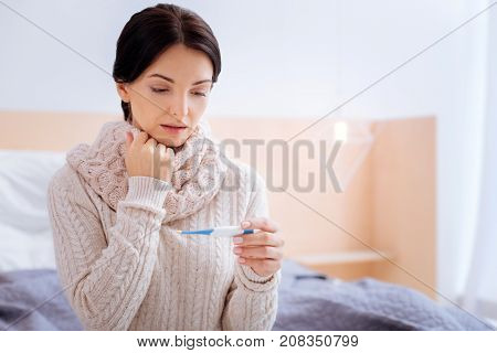 Sick time. Thoughtful young woman realizing her illness while looking at the temperature on a little screen of her thermometer