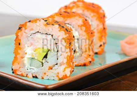 Clode up of California maki sushi with masago. Roll made of crab meat, avocado, cucumber and orange masago. Shallow depth of field.