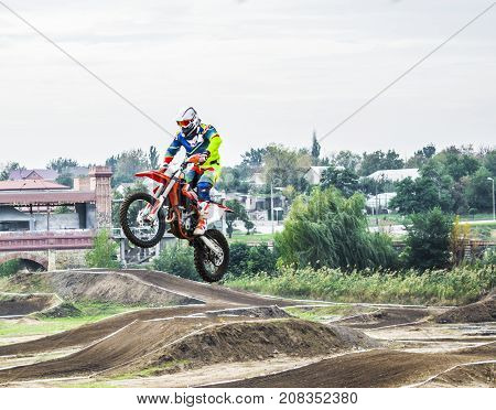 The Racer On A Motorcycle Participates In A Motocross Race, Jumps On A Springboard. He Took Off High