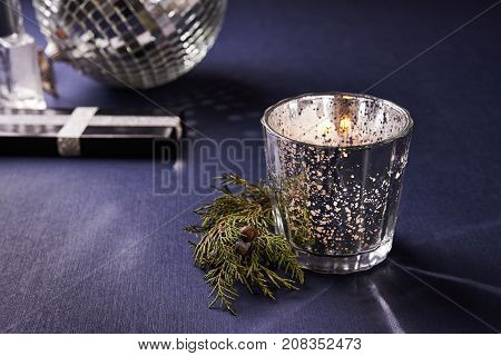 chrisnmas lights. candle in silver candlestick and gift box and disco ball out of focus