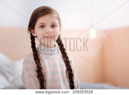 Looking glad. Cheerful friendly little girl with cute long bunches looking happy while being in her comfortable room