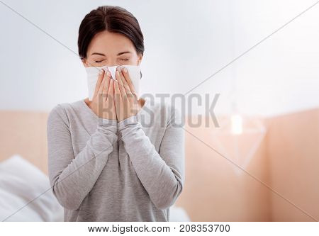 Terrible allergy. Tired young woman suffering from allergy while staying at home and sneezing