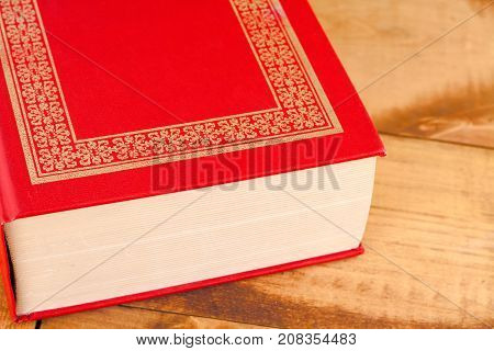Closed red book on wooden background .