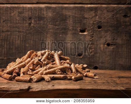 Pile of wooden pellets on a rustic wooden background alternative energy ecology concept