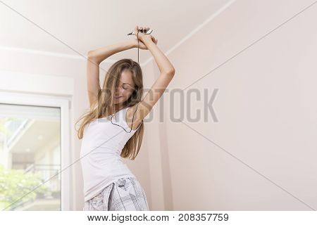 Beautiful cheerful young woman listening to the music wearing pajamas and a headphones dancing and jumping on the bed after waking up in the morning