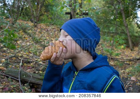 In the autumn in the woods, the boy eats a tasty bun