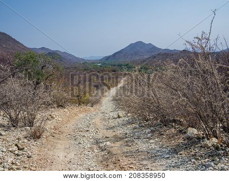 Very rough offroad track with large rocks and ruts leading along Kunene River between Kunene River Lodge and Epupa Falls, Namibia, Southern Africa