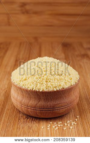 Couscous in wooden bowl on brown bamboo board closeup. Healthy dietary groats background.
