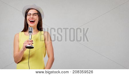 The girl is singing karaoke. A young woman in a hat with a microphone in her hand sings a song and laughs against a gray background.