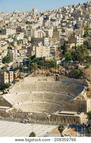 AMMAN, JORDAN - AUGUST 18, 2012: View to the ancient Roman theatre with the residential area buildings at the background in Amman, Jordan.