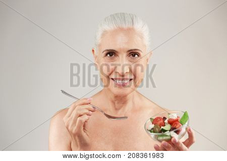 Beauty portrait of a smiling half naked elderly woman eating healthy greek salad from a bowl and looking at camera isolated over white background